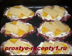 поверх апельсинов кладем кусочки сыра