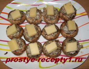Начиняем шампиньоны фаршем, сверху кладем сыр